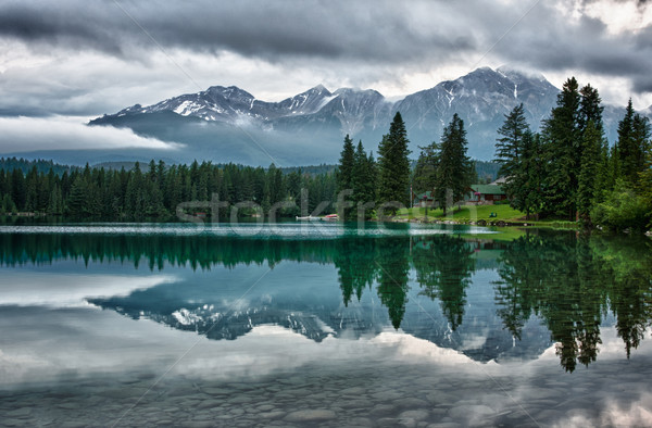 Foggy morning over Canadian Rocky Mountains perfectly mirrors in Stock photo © Klodien