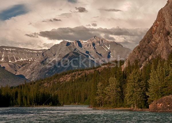 Dark clouds are moving in during sunset on the river near Banff  Stock photo © Klodien