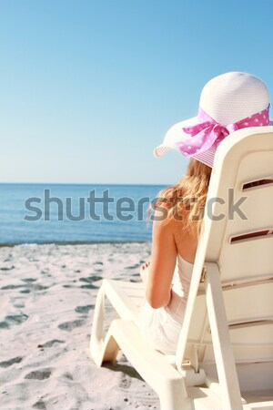 girl in hat is lying on a deck chair on the beach  Stock photo © koca777