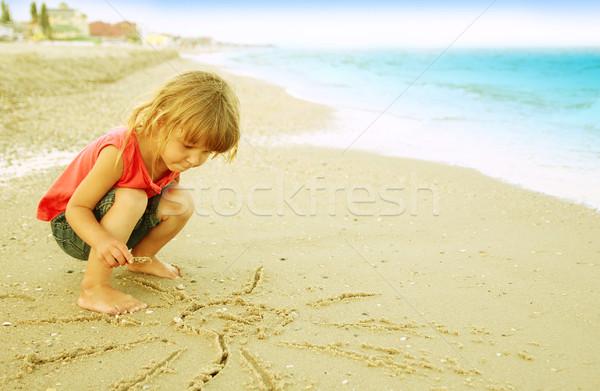 little girl draws a sun in the sand on the beach Stock photo © koca777