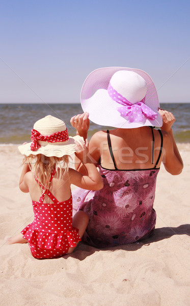 little girl sitting with her mother on the shore of the sea  Stock photo © koca777