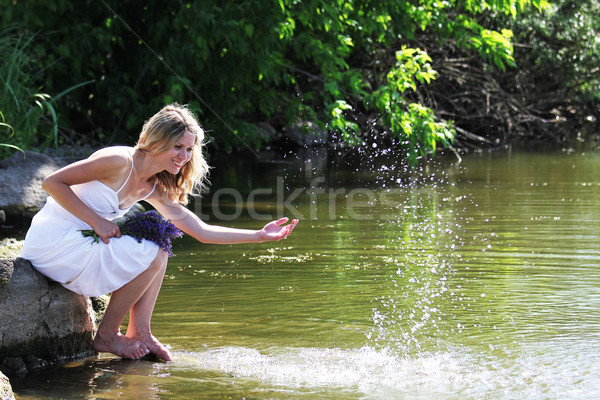 young woman sprinkles water near the lake Stock photo © koca777