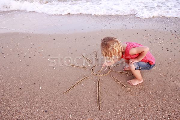 Little girl draws a sun in the sand  Stock photo © koca777
