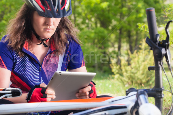 mountainbiker with her tablet in nature Stock photo © kokimk