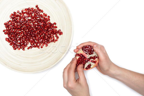 Full plate of peeled pomegranate seeds and a man de-seeding gran Stock photo © koldunov