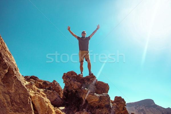 Handsome man on the giant rock Stock photo © konradbak