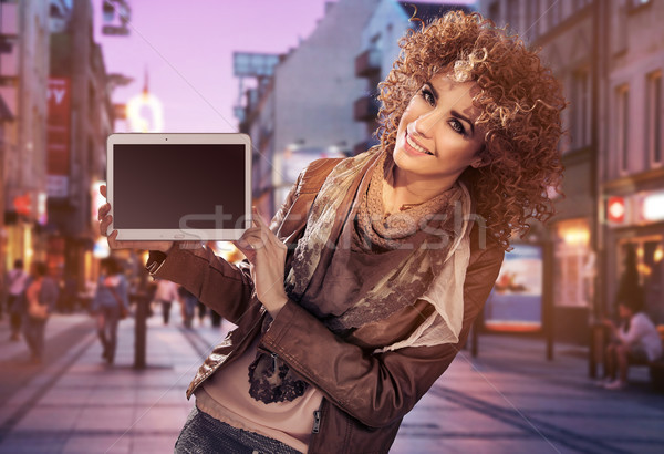 Alluring young woman holding a tablet Stock photo © konradbak