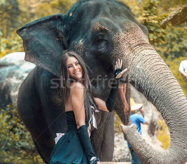 Pretty, smailing elephant trainer with her pet Stock photo © konradbak