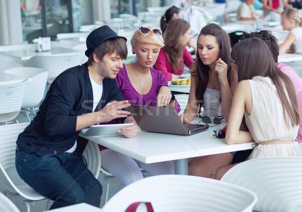 Cheerful friends browsing internet in a restaurant Stock photo © konradbak