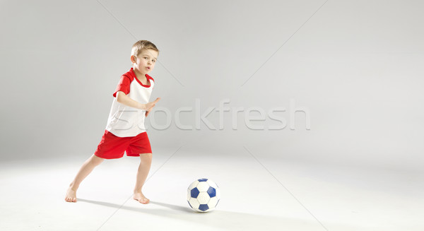 Little talented boy playing football Stock photo © konradbak