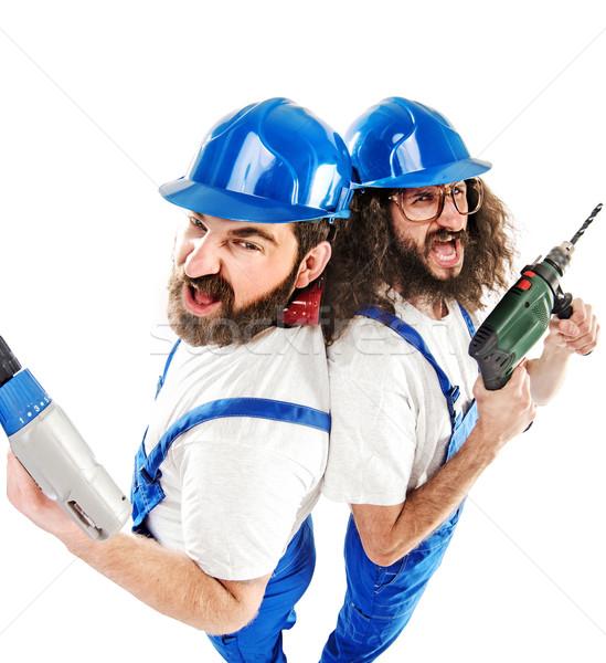 Conceptual picture of two builders while working Stock photo © konradbak
