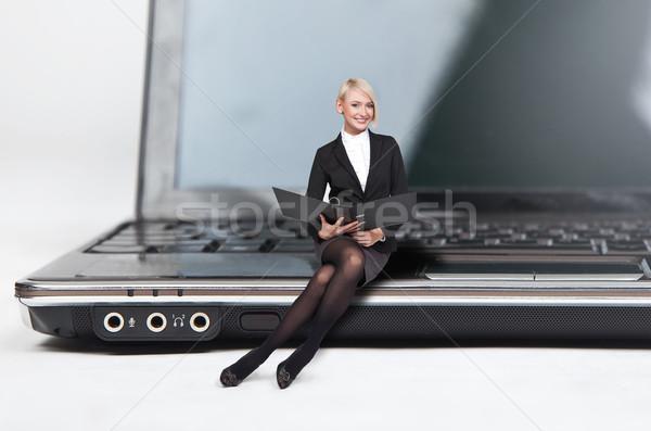 Closeup of pretty blond lady sitting on a laptop Stock photo © konradbak