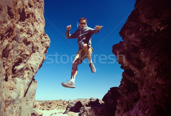 Cheerful man running on the desert mountains Stock photo © konradbak