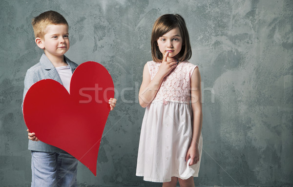 Cute little boy giving a heart to his sister Stock photo © konradbak