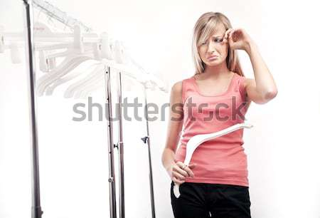Young pretty sad woman has nothing to put on Stock photo © konradbak