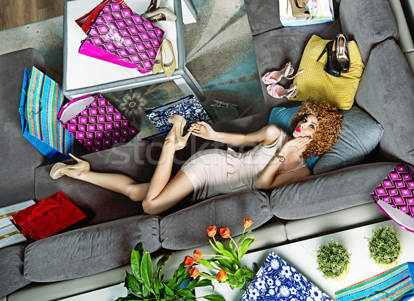 Portrait of a shopaholic lying among many shopping bags Stock photo © konradbak