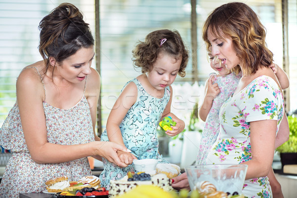 Young mothers making a cake with their daughters Stock photo © konradbak