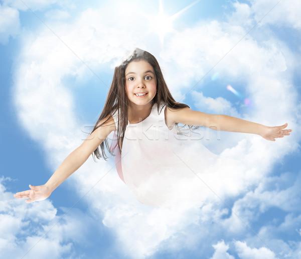 Girl flying through a heartshaped cloud Stock photo © konradbak