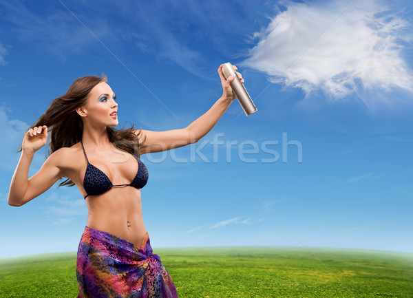 Young beautiful woman sprays clouds on a sunny day Stock photo © konradbak