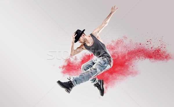 Conceptual picture of hip hop dancer among red dust Stock photo © konradbak