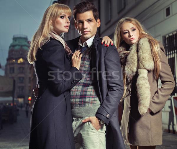Old fashion man with company of two cute women Stock photo © konradbak