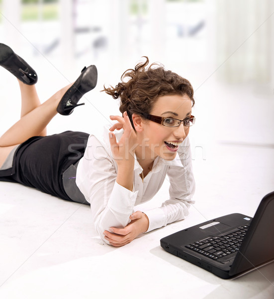 Young happy businesswoman with notebook rolling on the floor  Stock photo © konradbak