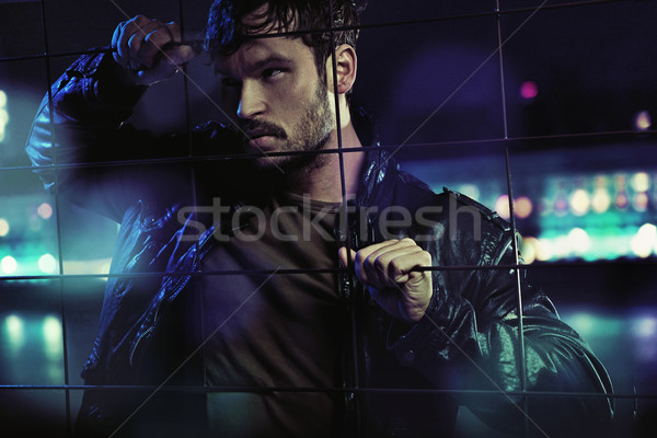 Handsome serious man trying to get out of fictious prison Stock photo © konradbak