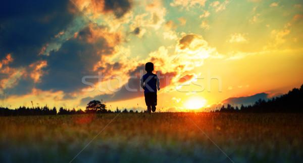 Cheerful boy running towards the sunset Stock photo © konradbak