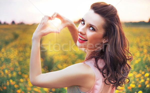 Beautiful woman making a heart sign Stock photo © konradbak
