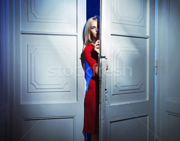 Blond vrouw voorzichtig opening deur dame Stockfoto © konradbak