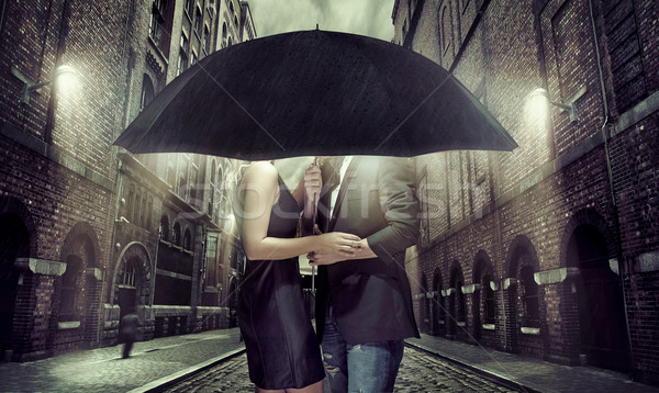 Young couple hiding themselves under the umbrella Stock photo © konradbak