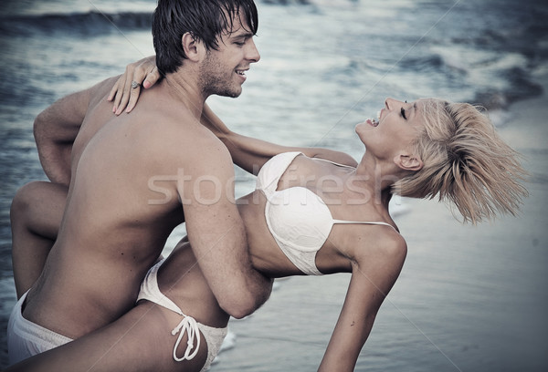 Joyful couple on the beach Stock photo © konradbak