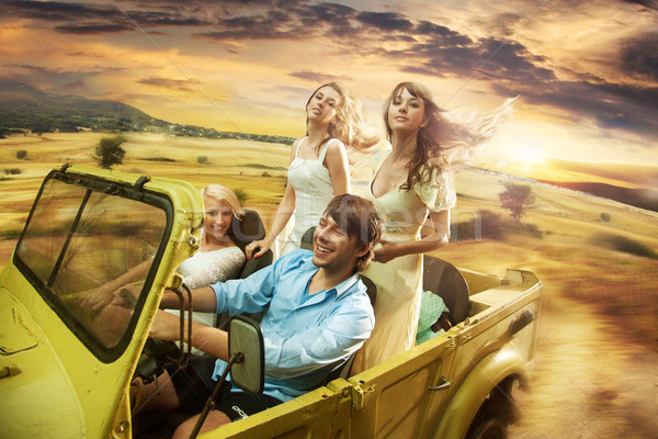 Group of cheerful friends driving a cabriolet Stock photo © konradbak