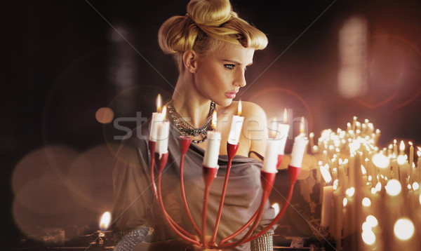 Stock photo: Serious blonde attractive woman keping candlestick