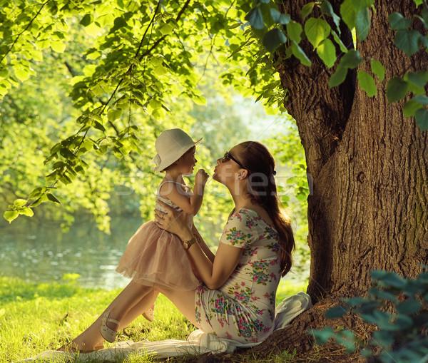 Brunette mother cuddling and kissing her daughter Stock photo © konradbak