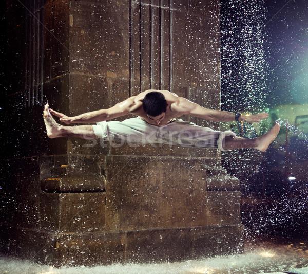 Muscular guy jumping and doing the splits Stock photo © konradbak