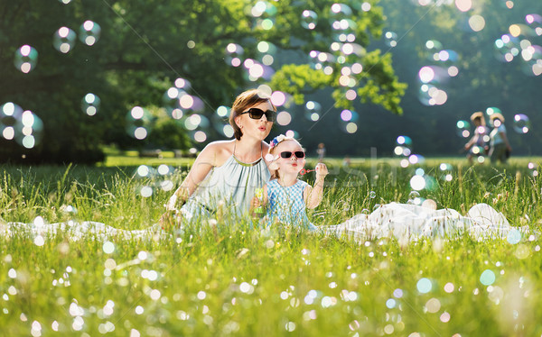 Mother and daughter family time, blowing soap-bubbles Stock photo © konradbak