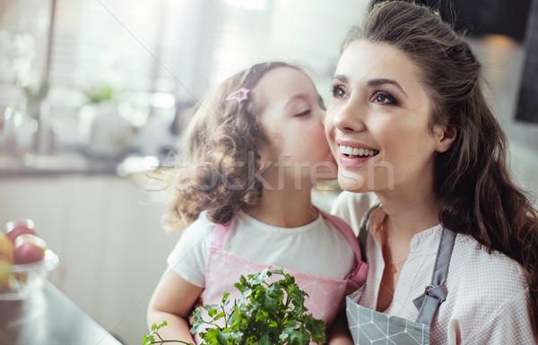 Mother and daughter holding herbs - kitchen shot Stock photo © konradbak