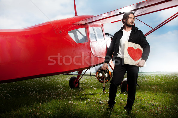 Young handsome man posing next to aeroplane Stock photo © konradbak