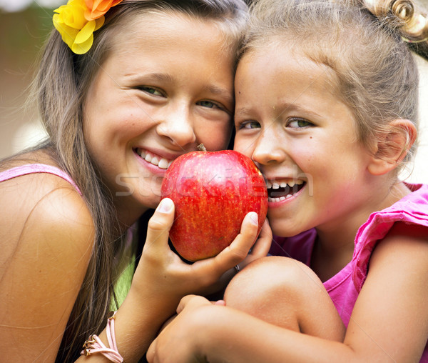 Two sisters sharing a big red apple Stock photo © konradbak