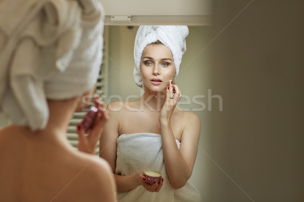 Blond woman rubbing gently a cream Stock photo © konradbak