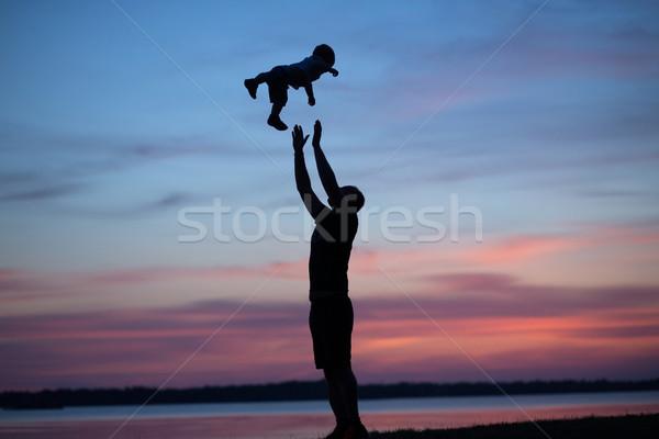 Silhouettes of father tossing his child Stock photo © konradbak