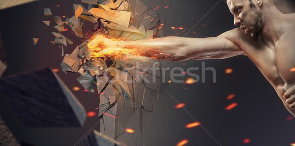 Muscular athlete crushing the wall Stock photo © konradbak