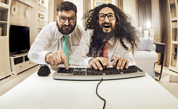 Two nerdy guys working with a computer Stock photo © konradbak