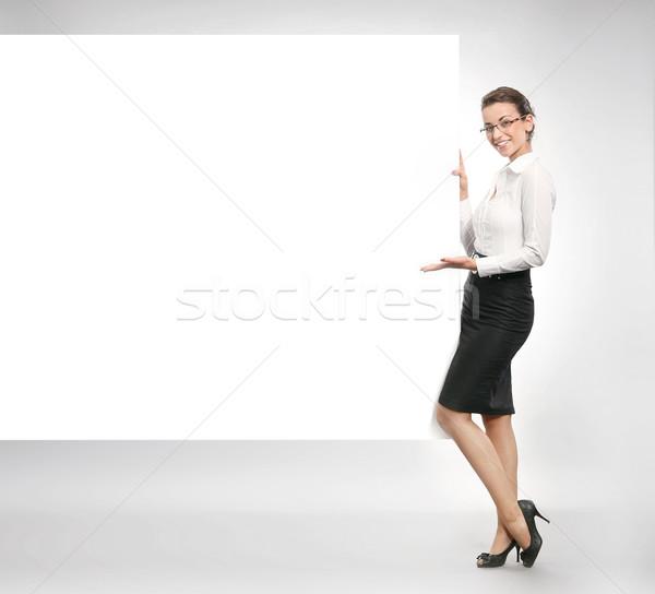 Attractive businesswoman showing empty white board Stock photo © konradbak