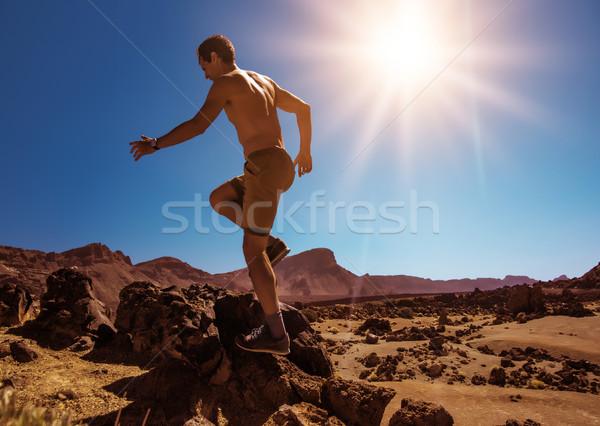 Handsome, muscular man running on the desert Stock photo © konradbak