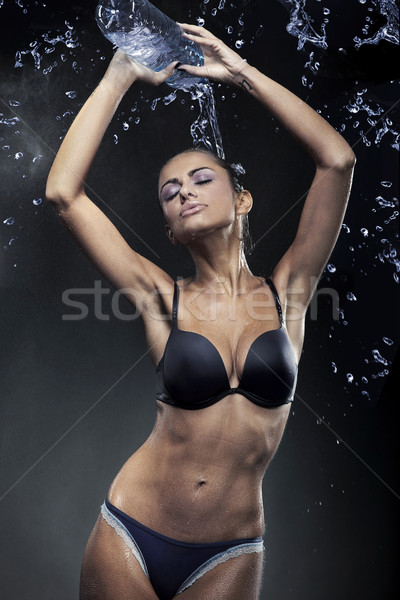 pretty young lady with a bottle of mineral water Stock photo © konradbak