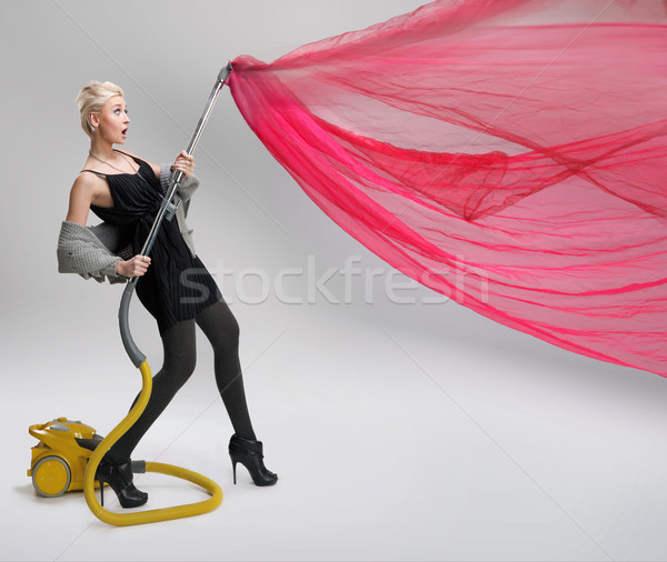Young woman using vacuum cleaner. Isolated. Stock photo © konradbak