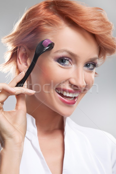Beautiful smiling woman using dermaroller on face Stock photo © konradbak