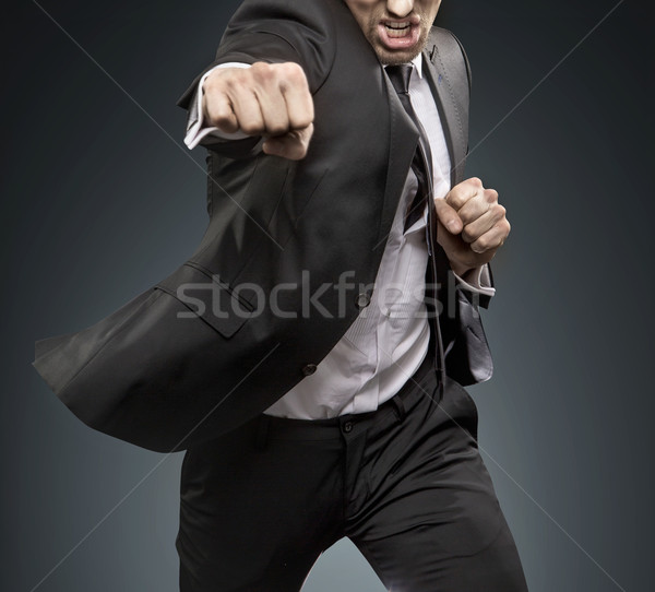 Brave businessman fighting againts challengers Stock photo © konradbak